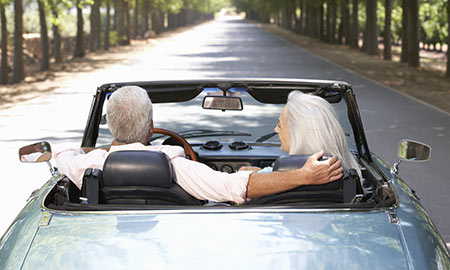 Older couple in convertible driving down country road