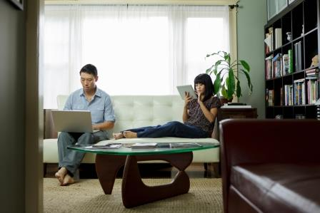Couple sitting on couch looking at their personal electronic devices