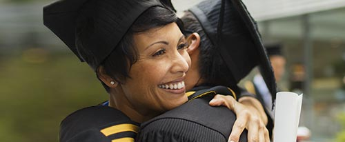 adult woman in a cap and gown hugging fellow graduate