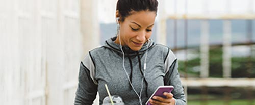woman in athletic clothing listening to music outside