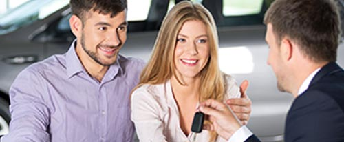 happy couple receiving car keys from salesman